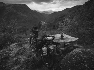 Black and white photograph of a touring bicycle at a rest stop, view overlooking valley below
