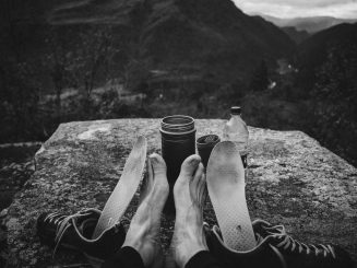 Black and white photograph of feet being warmed nex to a small camping stove