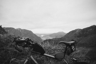 Black and white photograph of a mountain view behind a bicycle