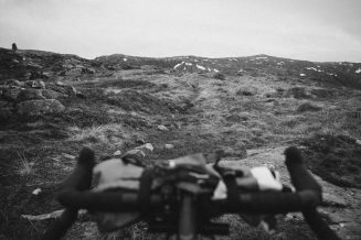 Black and white photograph over the handlebar of a bicycle and the view in front of it