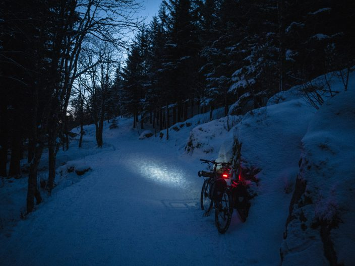 Bicycle, with lights on, on a snowy track in the woods at dusk