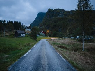 Rural road at dusk, farm and mountains in background.