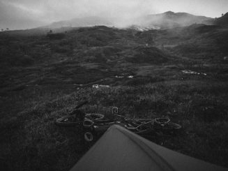 Morning landscape with tent in foreground, in black and white.