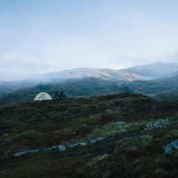 Morning landscape showing tent and distant fog in mountain landscape.