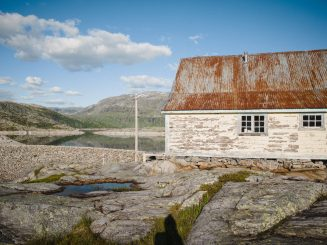 Weathered house in rugged mountain landscape