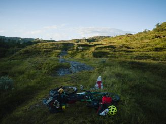 bike with camping gear and tracks in evening sunlight
