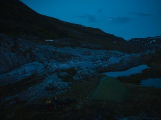 touring bicycle and tent at dusk in the mountains