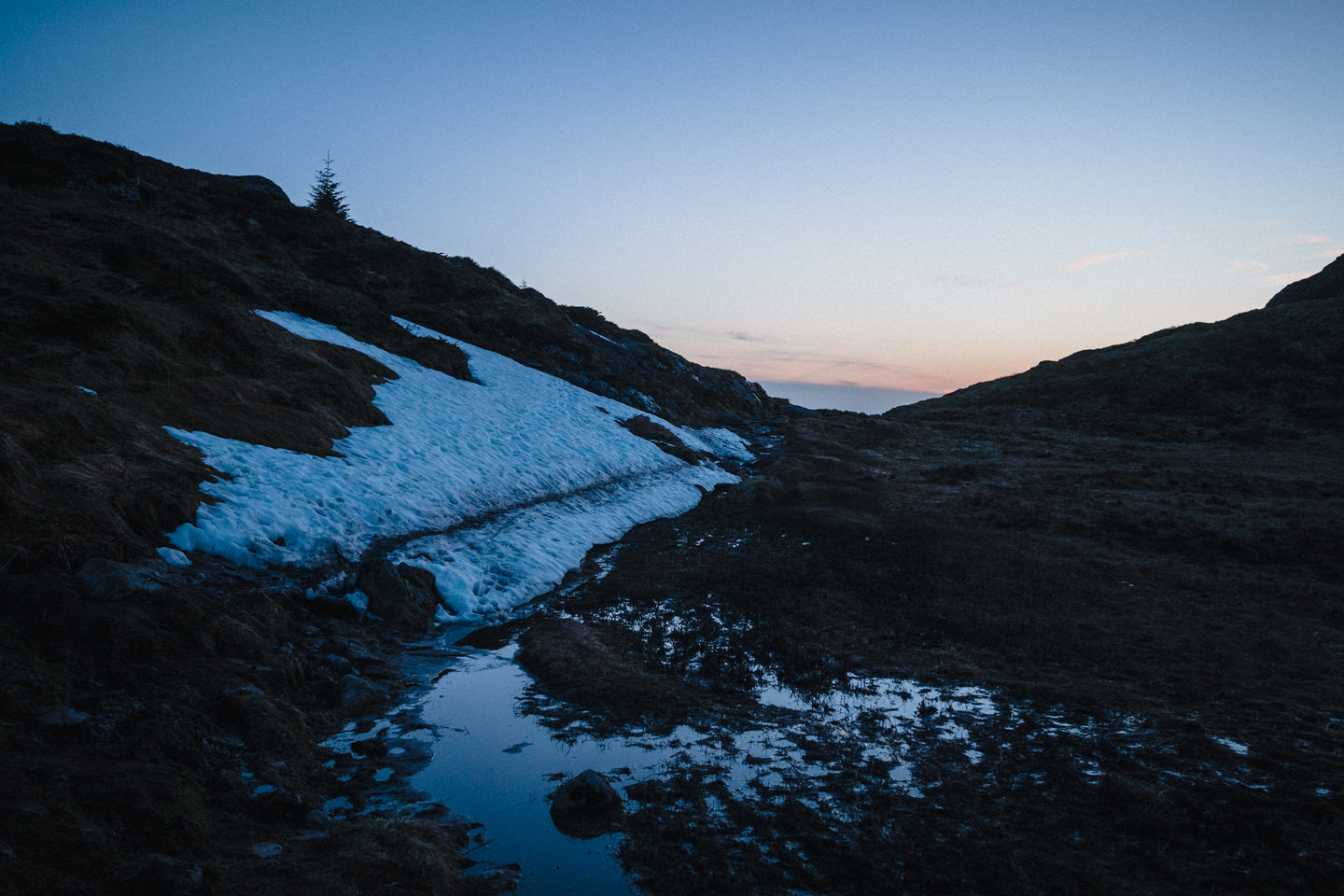 A pile of snow at dusk, with a footpath through it