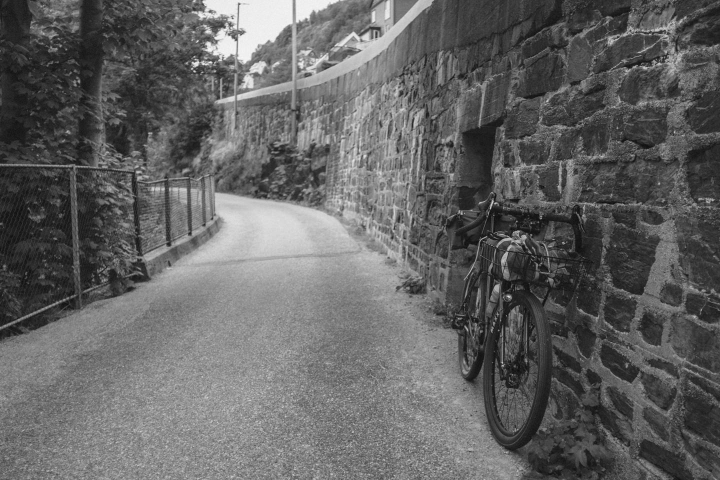 bicycle leaning against wall, seen from the front, in black and white
