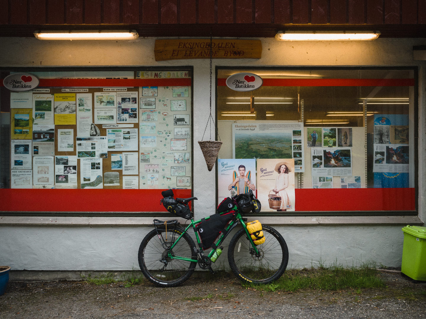 Loaded touring bike next to a rural grocery store, Norway