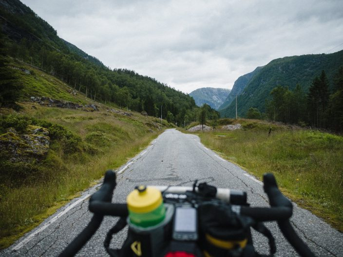 view over bicycle handlebars and narrow tarmac road