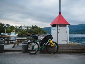 Touring bicycle by the fjord. Boat in the background.