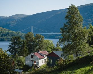view of a farm, mountains and fjord with a bridge over it