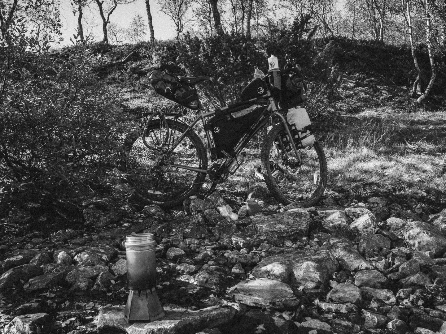 Touring bicycle and a camping stove outside, in black and white.