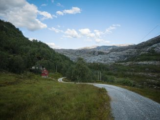 S-formed gravel road, mountain landscape in distance